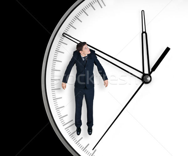 Businessman hangs on an arrow of clock Stock photo © zeffss