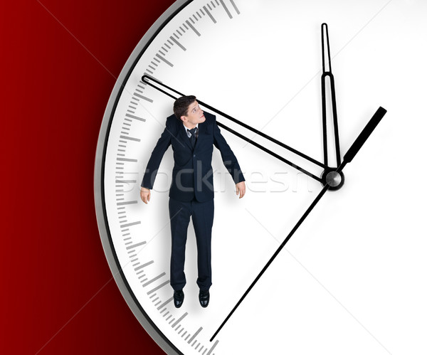 Stock photo: Businessman hangs on an arrow of clock