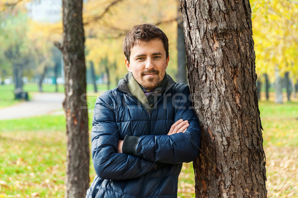 Handsome guy leaned against a tree in autumn park Stock photo © zeffss