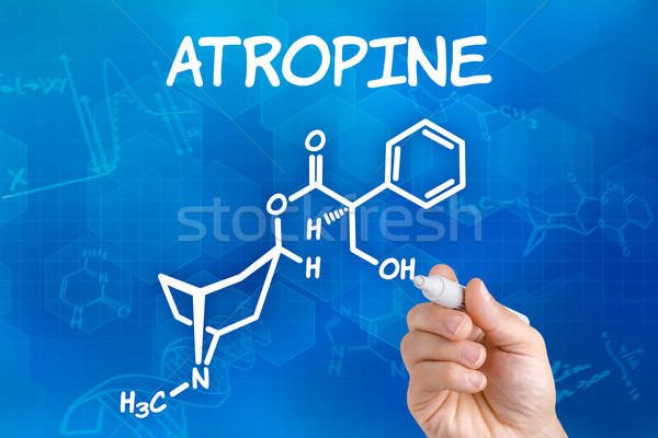 Hand with pen drawing the chemical formula of Atropine Stock photo © Zerbor