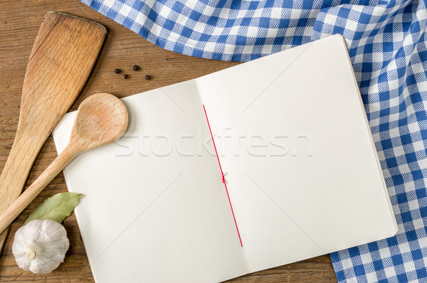 Book with wooden spoons on a blue checkered tablecloth Stock photo © Zerbor