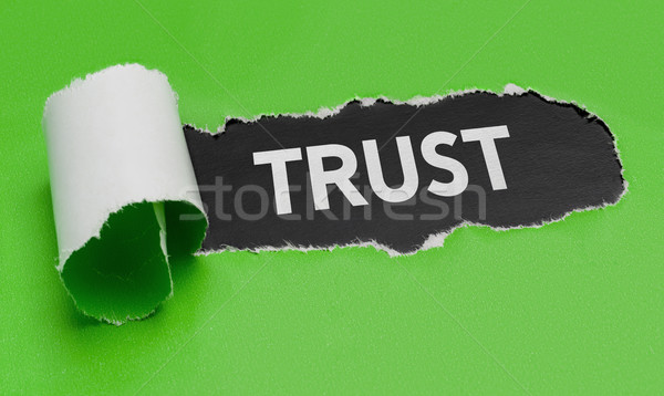 Stock photo: Torn green paper revealing the word Trust