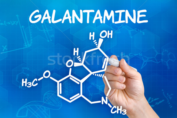 Hand with pen drawing the chemical formula of Galantamine Stock photo © Zerbor
