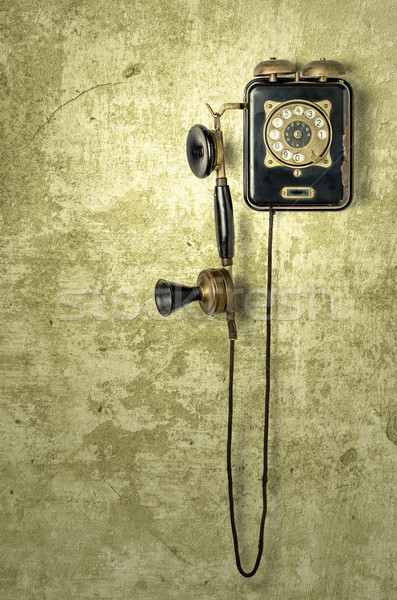 antique telephone on a grungy yellow wall Stock photo © Zerbor