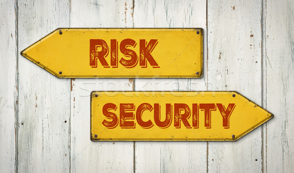Direction signs on a wooden wall - Risk or Security Stock photo © Zerbor