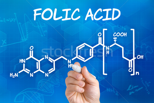 Hand with pen drawing the chemical formula of folic acid Stock photo © Zerbor