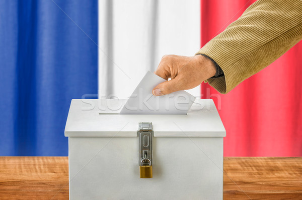 Man putting a ballot into a voting box - France Stock photo © Zerbor