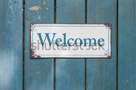 Old metal sign in front of a rustic wooden wall - Welcome Stock photo © Zerbor