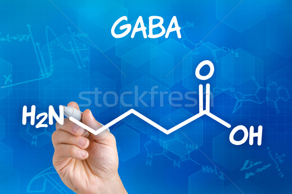 Hand with pen drawing the chemical formula of GABA Stock photo © Zerbor