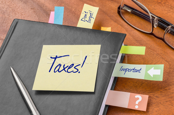 Planner with sticky note - Taxes Stock photo © Zerbor