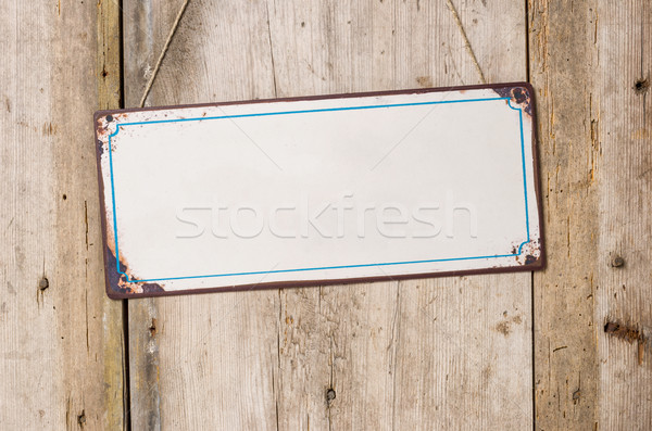 Empty metal sign in front of a rustic wooden wall  Stock photo © Zerbor