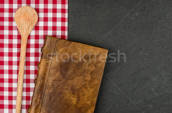 Wooden spoon and cookbook on a slate plate  Stock photo © Zerbor