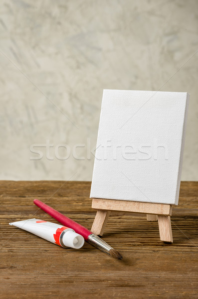 Easel with a blank canvas, paint and brush Stock photo © Zerbor