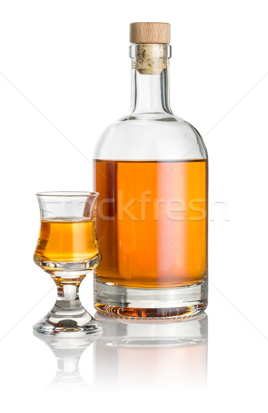Bottle and schnapps glass filled with amber liquid Stock photo © Zerbor