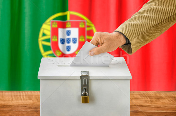 Man putting a ballot into a voting box - Portugal Stock photo © Zerbor