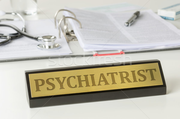 Name plate on a desk with the engraving Psychiatrist Stock photo © Zerbor