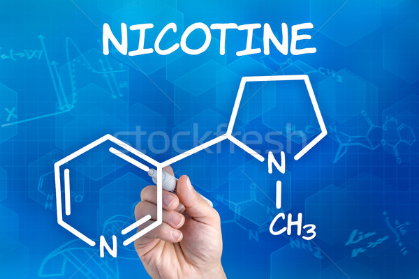 hand with pen drawing the chemical formula of nicotine Stock photo © Zerbor