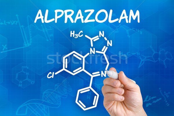 Hand with pen drawing the chemical formula of Alprazolam Stock photo © Zerbor