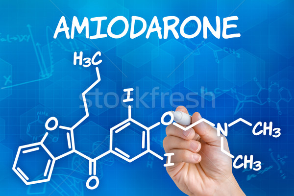 Hand with pen drawing the chemical formula of Amiodarone Stock photo © Zerbor