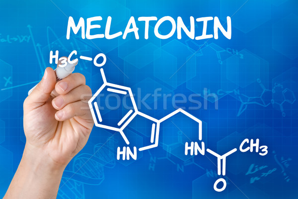 Hand with pen drawing the chemical formula of melatonin Stock photo © Zerbor