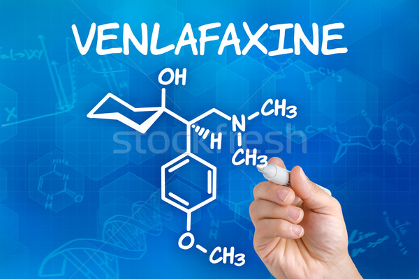 Hand with pen drawing the chemical formula of Venlafaxine Stock photo © Zerbor