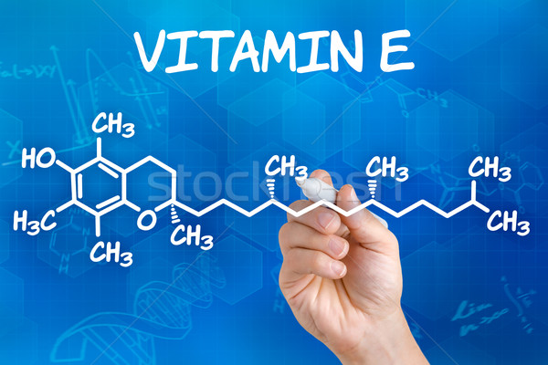 Hand with pen drawing the chemical formula of Vitamin E Stock photo © Zerbor