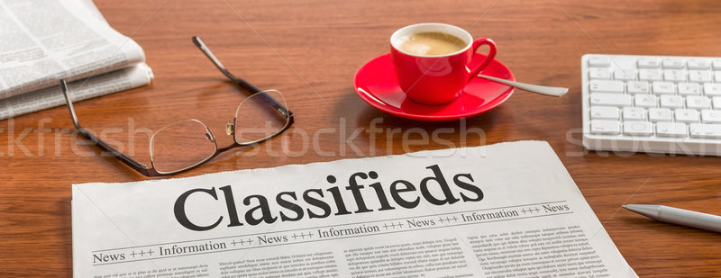 A newspaper on a wooden desk - Classifieds Stock photo © Zerbor