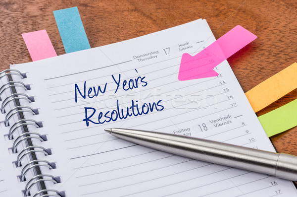 Daily planner with the entry New Years Resolutions Stock photo © Zerbor