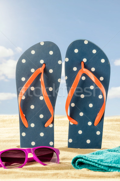 Stock photo: Flip Flops in the sand with sunglasses and a beach towel