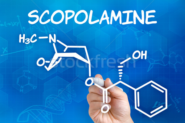 Hand with pen drawing the chemical formula of Scopolamine Stock photo © Zerbor