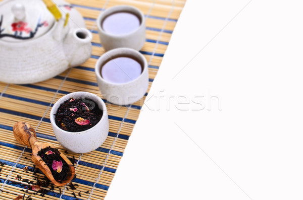 Black tea with rose petals on white background Stock photo © zia_shusha