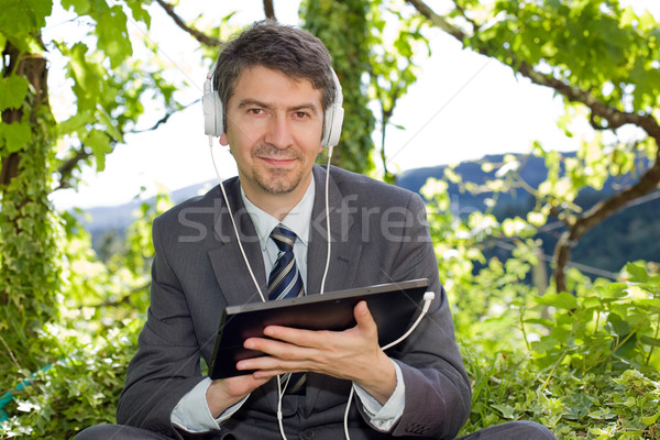 ストックフォト: ビジネスマン · 幸せ · デジタル · タブレット · ヘッドホン · 屋外