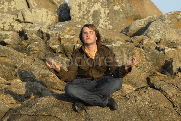 Stock fotó: Jóga · fiatalember · meditál · ül · kövek · naplemente