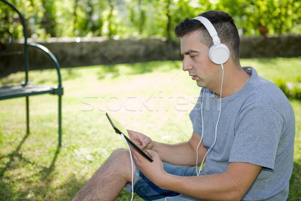 ストックフォト: 男 · タブレット · 若い男 · ヘッドホン · 屋外