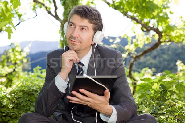 Işadamı mutlu dijital tablet kulaklık açık havada Stok fotoğraf © zittto