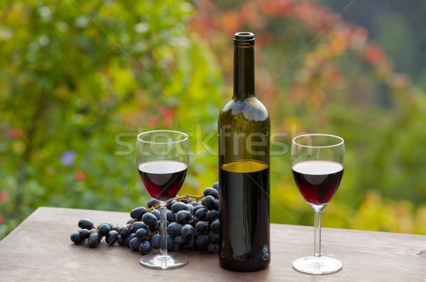 ストックフォト: 赤ワイン · ワインボトル · ブドウ · 木製のテーブル · 屋外 · 太陽
