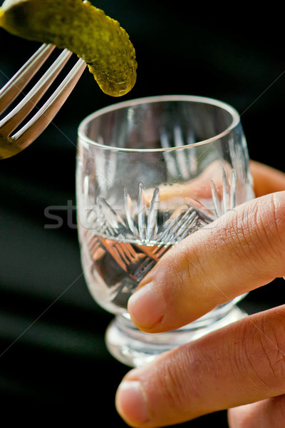 glass of vodka and pickled cucumber on a fork in male hands. Stock photo © zoryanchik