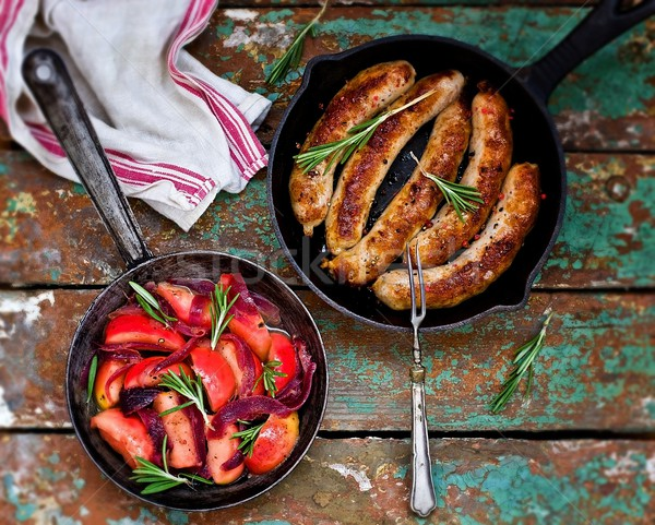 fried sausages with apples, onions and rosemary in a frying pan  Stock photo © zoryanchik
