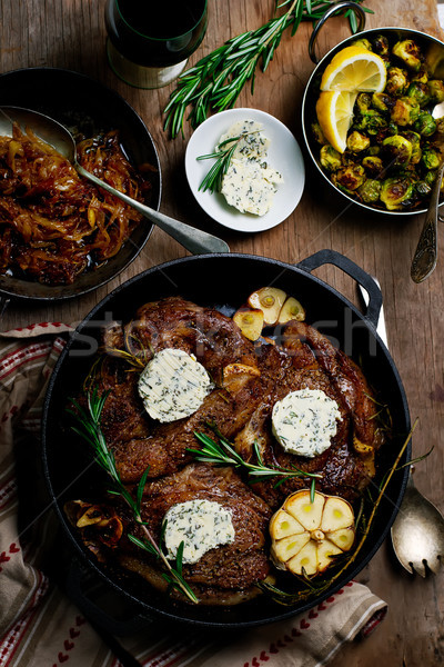A SKILLET SEARED RIBEYE WITH HOMEMADE HERB BUTTER, CARAMELIZED ONIONS, AND FRIED BRUSSEL SPROUTS Stock photo © zoryanchik