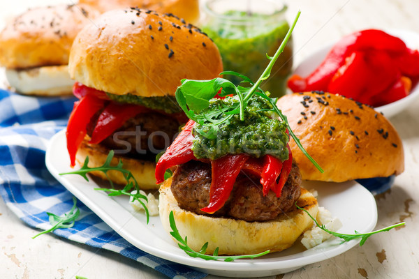 feta stuffed turkey burgers with arugula pesto and roasted red peppers. Stock photo © zoryanchik
