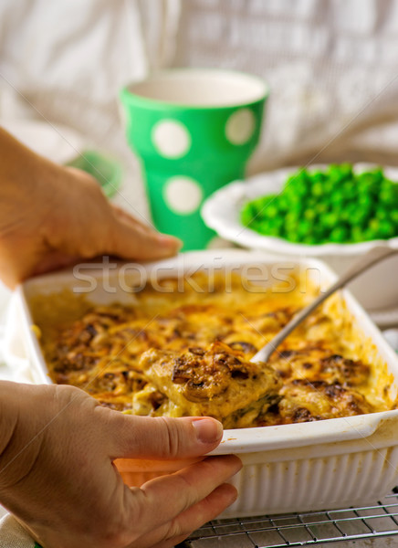 baked pudding with fish and mushrooms in a ceramic form for roasting and green peas in a bowl. Stock photo © zoryanchik