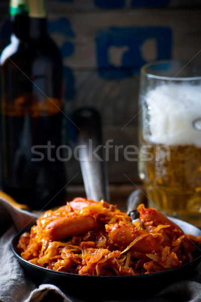 stewed cabbage with sausages in a vintage frying pan and a mug with beer. Stock photo © zoryanchik