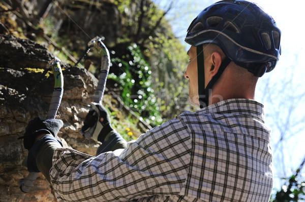 Climbing man with hooks on cliff Stock photo © zurijeta
