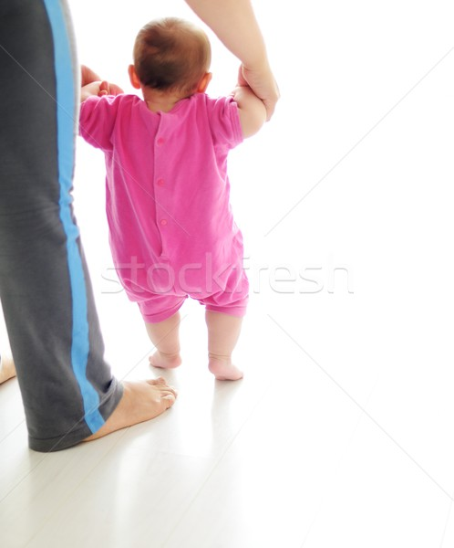 Baby taking first steps with mother help on white background Stock photo © zurijeta