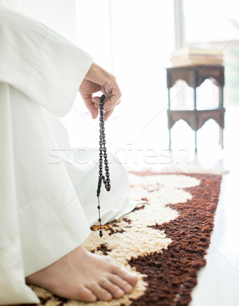 Arabic aged man sitting on ground using traditional beads Stock photo © zurijeta