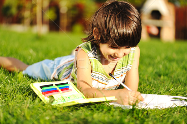 Stock photo: Young boy outdoors on the grass reading a book, writting and drawing