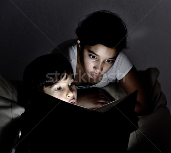 Cute kids reading a book at night Stock photo © zurijeta