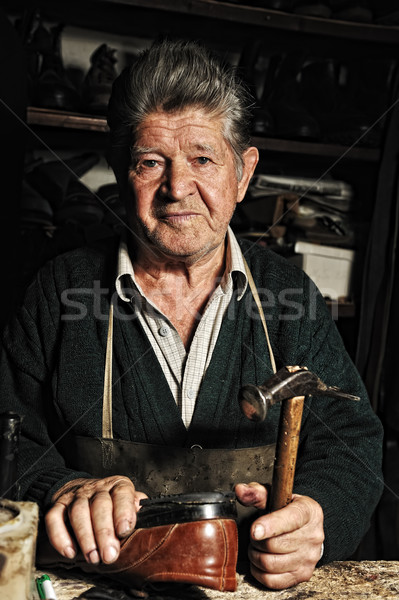 Old man, shoemaker, repairing old handmade shoe in his workshop Stock photo © zurijeta