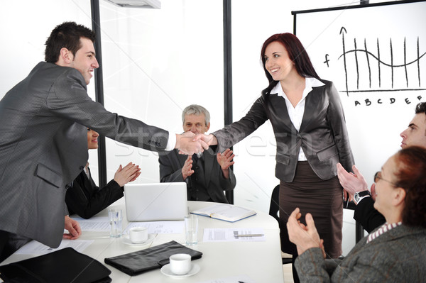 Business partners shaking hands after making deal while their co-workers applauding Stock photo © zurijeta