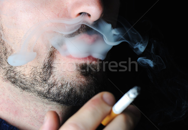Man smoking in dark with visible smoke Stock photo © zurijeta